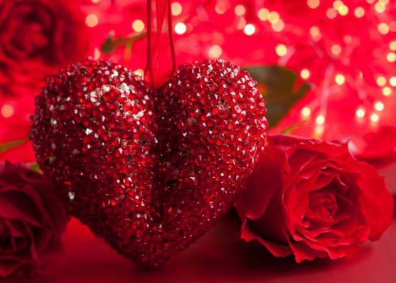 Foto de un corazón rojo y brillante con una rosa al lado, recortado sobre un fondo festivo de color rojo