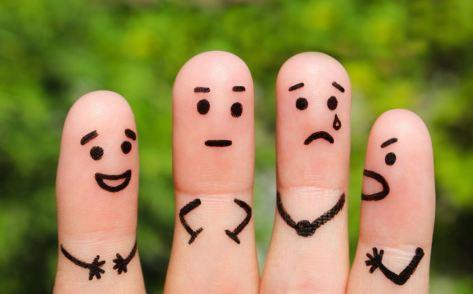 Foto de cuatro dedos de la mano donde en cada uno de ellos está pintado una emoción