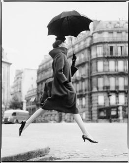 Foto artística de una mujer dando un salto y con un paraguas abierto en una mano.