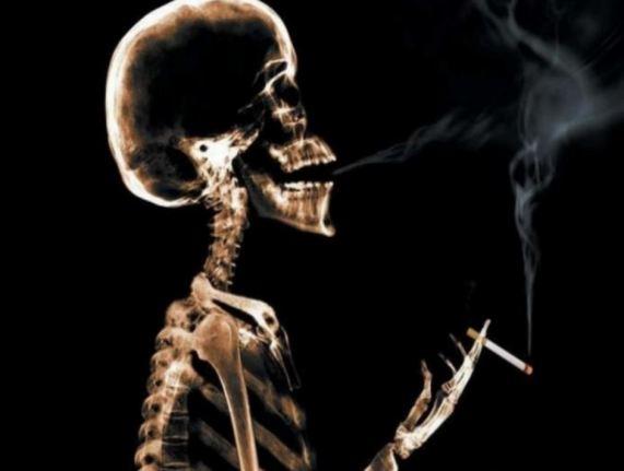 Imagen de perfil de un esqueleto humano fumando