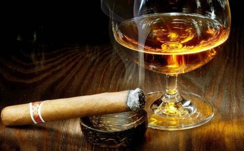 Imagen de una copa de licor con un puro encendido sobre un cenicero pequeño de madera