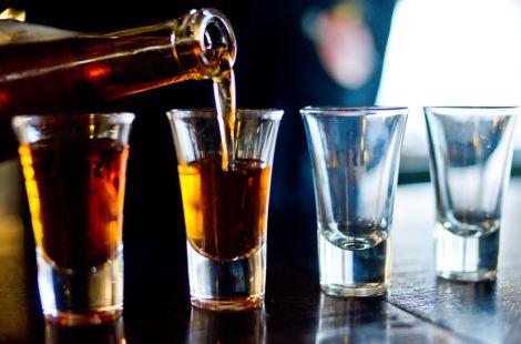 Imagen de cuatro chupitos que se van rellenando de alcohol de una botella