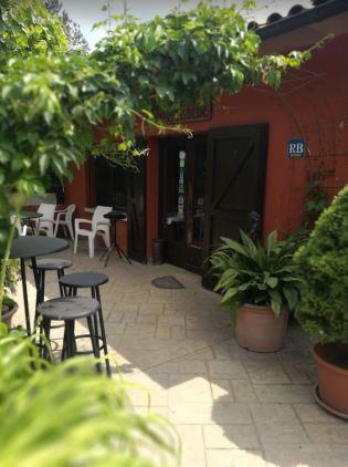 En la foto aparece la entrada del restaurant con muchas plantas y unas sillas en una de sus terrazas