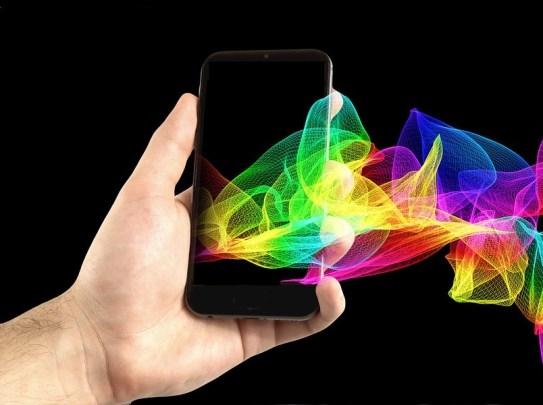 Una composición digital donde se ve una mano con un teléfono móvil del que salen unas gráficas en forma de malla tridimensional con los colores del arcoiris