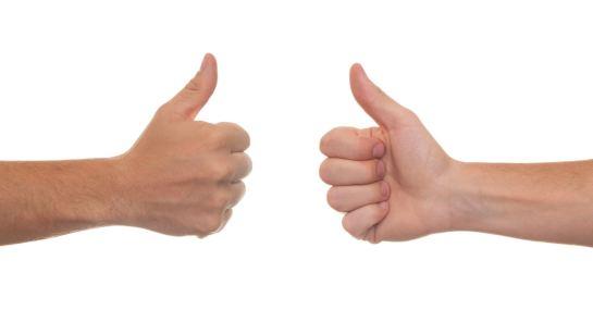 Imagen de dos manos frente a frente con el pulgar levantado hacia arriba, recortadas sobre un fondo blanco