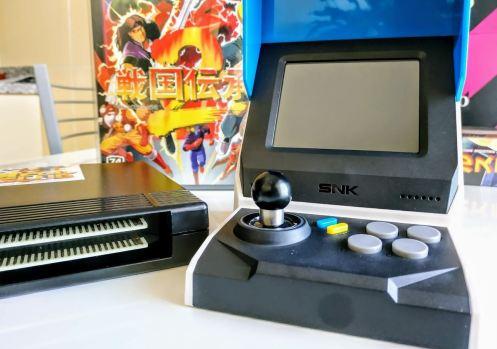 En la foto se muestra la Neo-Geo Mini comparada con un cartucho original de la Neo-Geo primigenia