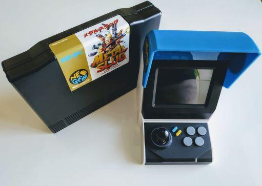 En la foto un cartucho original del Metal Slug y la Neo-Geo mini