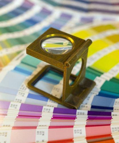 En la foto una lupa cuenta hilos sobre una carta de colores Pantone (R)