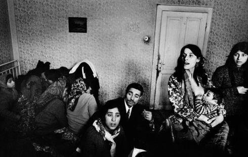 Foto de una familia con varios miembros en una habitación, todos están ajenos a la cámara.