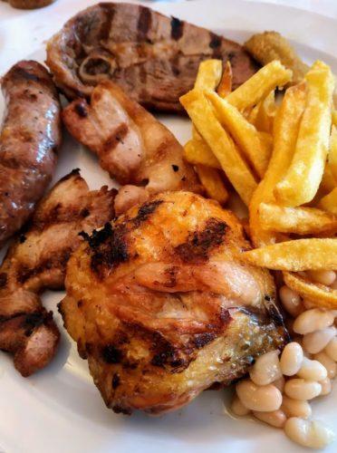 Excelente parrillada de carne compuesta por patatas fritas, judías blancas, pollo, cordero, cansalada y butifarra