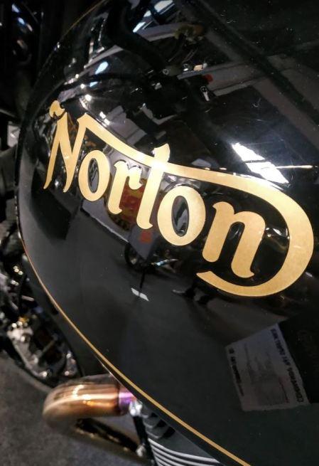 El logotipo de Norton en color dorado sobre una Norton Comando en color negro