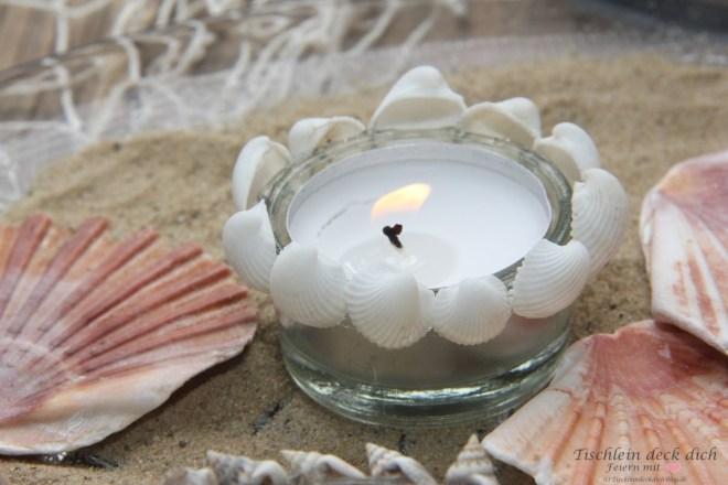 maritime-Kerzdendeko mit kleinen Muscheln und Teelichtgläsern