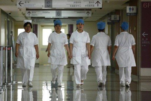 Illustration: un groupe d'infirmières se promène le long d'un couloir dans un hôpital de Pékin le 29 Juillet 2013.