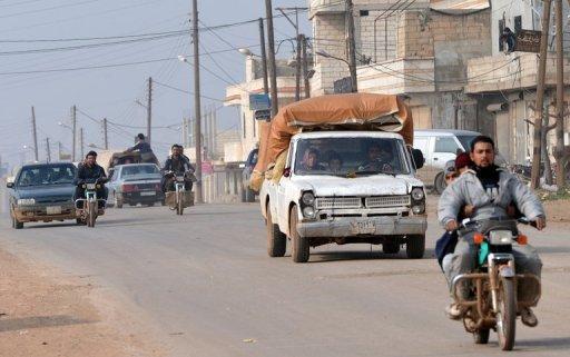 Les résidents conduire des motocycles et des voitures pour fuir lors des combats entre les rebelles et les forces du régime près de Hama, le 27 Janvier 2013.