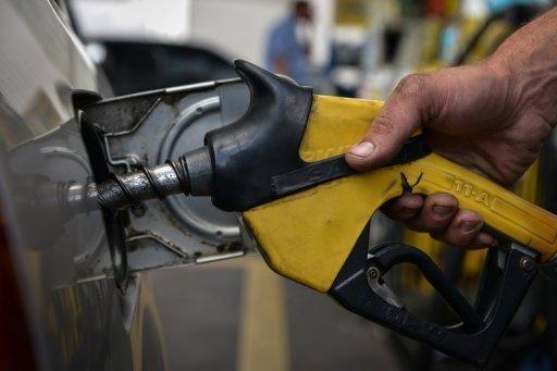 Un travailleur remplit le réservoir d'un véhicule à une station d'essence de Sao Paulo, Brésil, du 25 mai 2012.