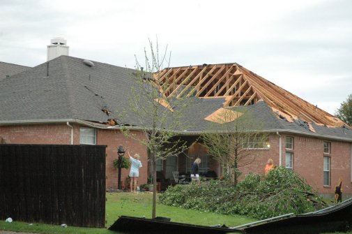 Suburban house with shingles and roof structure blown away.