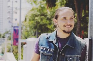 In front of an out of focus background of green trees, a person wearing a purple shirt underneath a blue jean vest smiles warmly, looking off to the right.