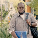 An advocate of TM Health LA stands holding a blue 'Networking' textbook and a black backpack in front of a vibrant green courtyard full of trees, bushes and flowers.