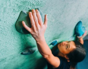 Woman Climbing Up On Wall In Gym