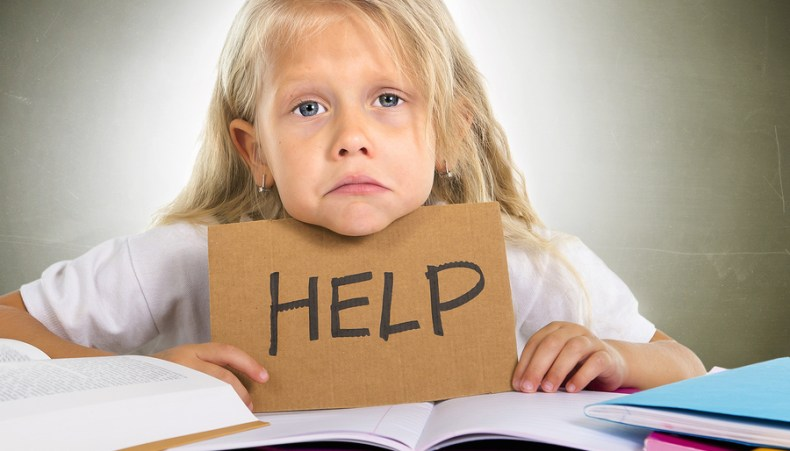 Sweet Little School Girl Holding Help Sign In Stress With Books