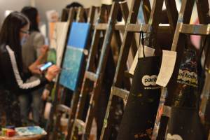 Photo of easels and people painting.