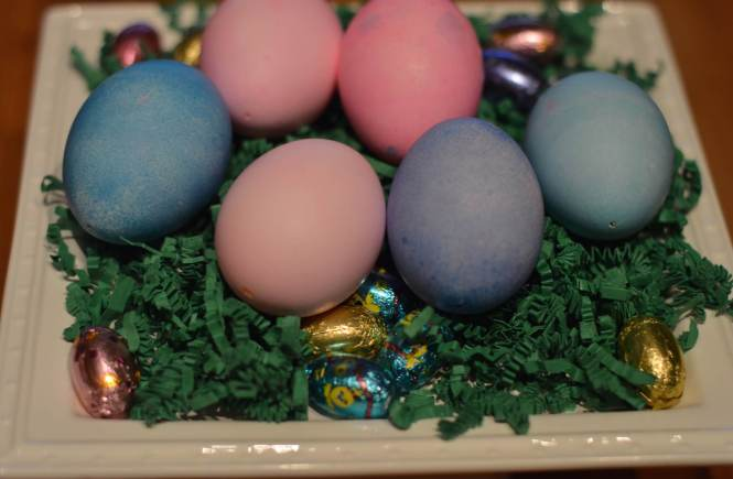 Easter eggs in their finalized state displayed on fake grass.
