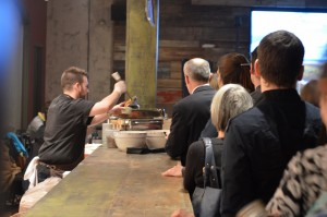 A photo of a cook serving the line of attendees a bowl of soup.