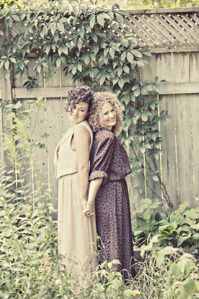 Amanda and Angie posing together with a greenscape backdrop.