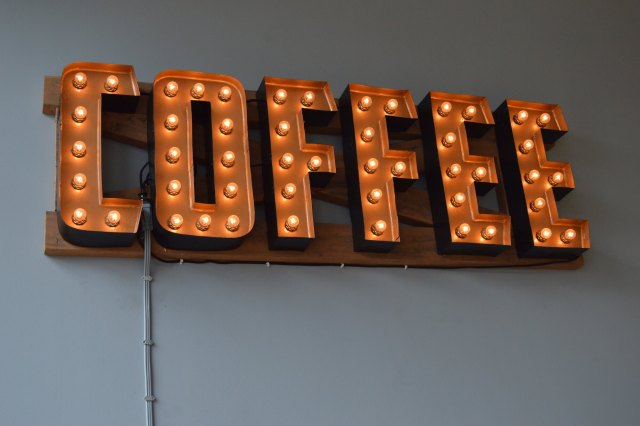 The word coffee is spelled out on a sign that lights up with a marquee affect.