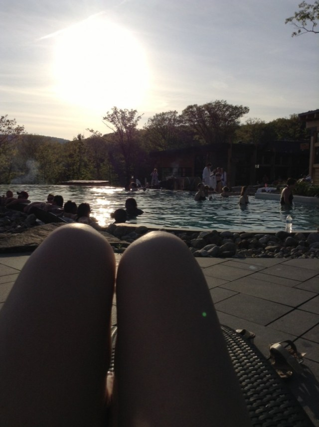 Sunseting in the background as people enjoy the infinity pool.