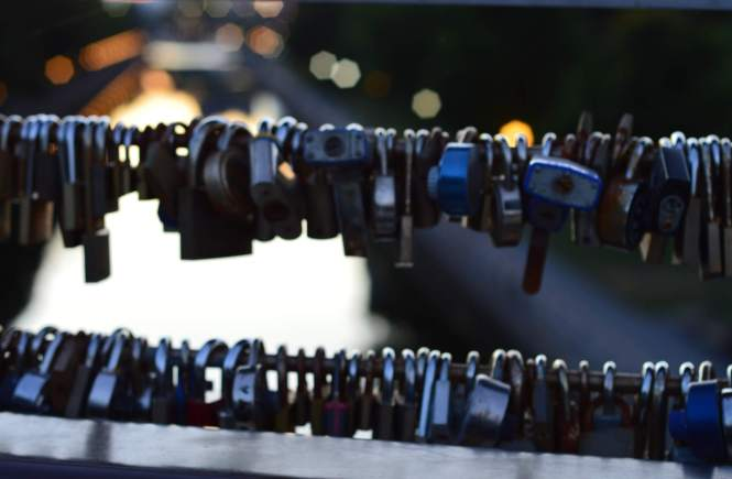 Photo of a railing with locks set against the sunset.