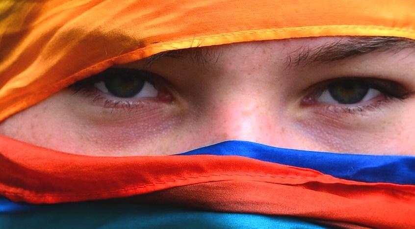 Eine Frau hat das Gesicht mit bunten Tüchern verborgen, nur die Augen sehen heraus