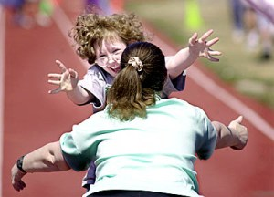 Cindy Hasselquist, 10, runs into the waiting arms of her mother, Rose, after completing the 50 meter dash during an Special Olympics events.