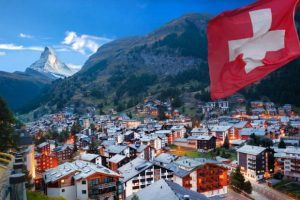 swiss-town-with-flag-of-switzerland-swiss-alps-matterhorn-in-background-300x200