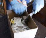 Using a slit cut in a cardboard box to contain the mess when using chemical paint stripper.