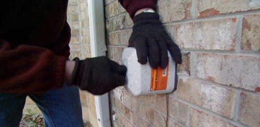 Installing an insulated foam hose bibb cover on an outdoor spigot.