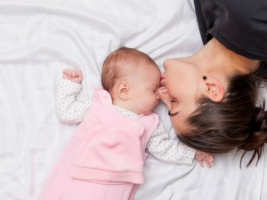mom smeeling baby while lying in bed