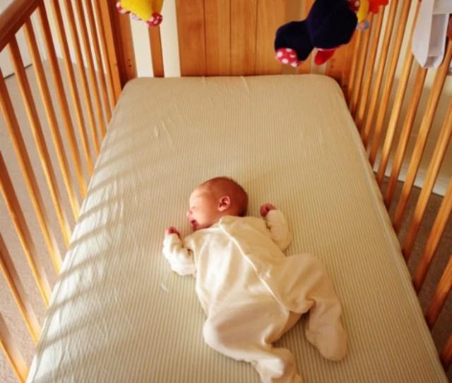 A Baby Sleeping In A Crib