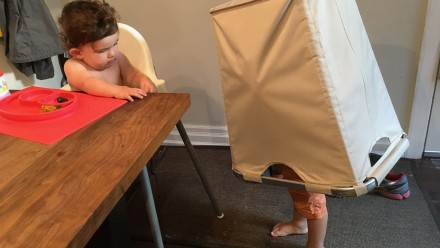 Kid playing with laundry hamper while baby eats at the table in a high chair
