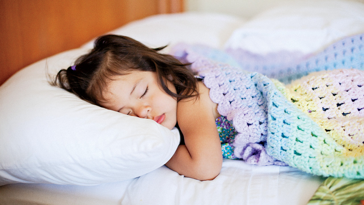 a little girl sleeping in bed for a story on milestone development