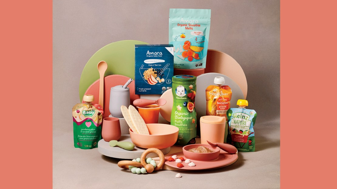 An array of packaged baby foods by Gerber, Baby Gourmet, Heinz and more with pretty bowls, plates and utensils in peach, clay, lime green and rose colours