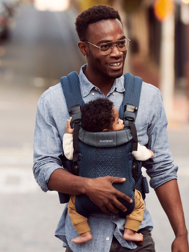 A photo of a parent in a blue button up shirt wearing a blue BabyBjörn Harmony baby carrier with their child inside,