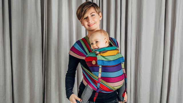A parent wearing a multi-coloured WrapTai baby carrier with their baby inside. They are standing against a light grey curtain.