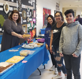 Mandy Reed (Vice-Principal) serving food to students Koussay Alai (Grade 11), Priya Bhatti (Grade 12) and Amanda Uy (Grade 12) at the food table.
