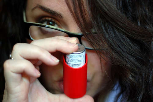 Chica usando un inhalador contra el asma