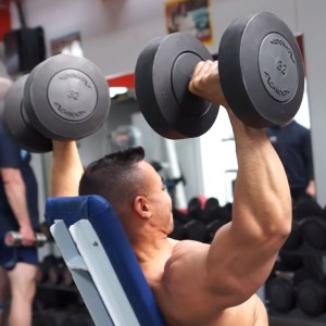 Hombre haciendo press militar con mancuernas en gym