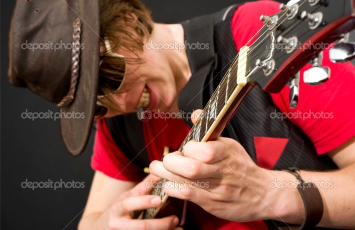A trendy looking guitar player during a heavy guitar solo. Selective focus on the musicians left hand