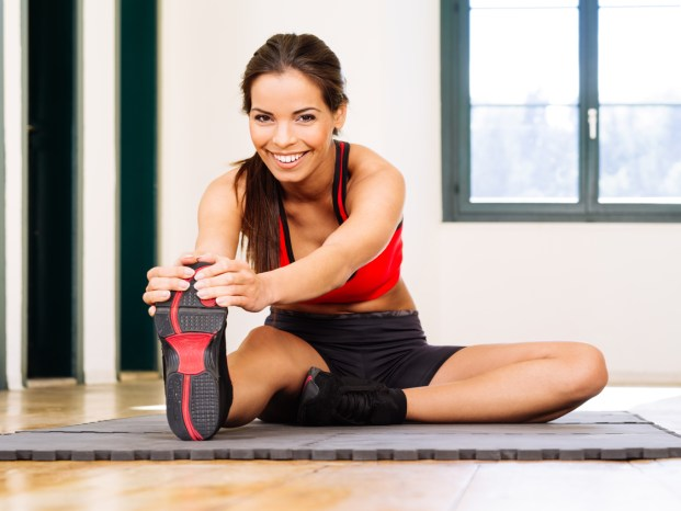 Photo of a beautiful female stretching on the floor sitting on a mat.