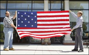 Tom Apel, left, and Richard Baranowski display a 15-star flag to be raised during a Monday ceremony at Perrysburg's Way Public Library to commemorate the beginning of the War of 1812.