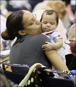 Roslyn Frank de Grosse Pointe, Michigan, beijos de seu filho de 2 meses de idade, Jacob Peterson, enquanto escuta a um alto-falante durante o evento O Morrison lâmina / ANDY. Ampliar